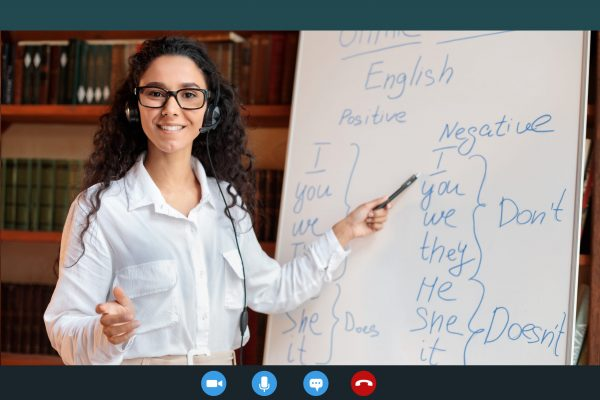 Distance Education And Technology. Woman In Glasses And Headset Having Video Conference, Teaching Foreign Languages, Talking To Camera During Web Call, Pointing At Whiteboard With Grammar Rules
