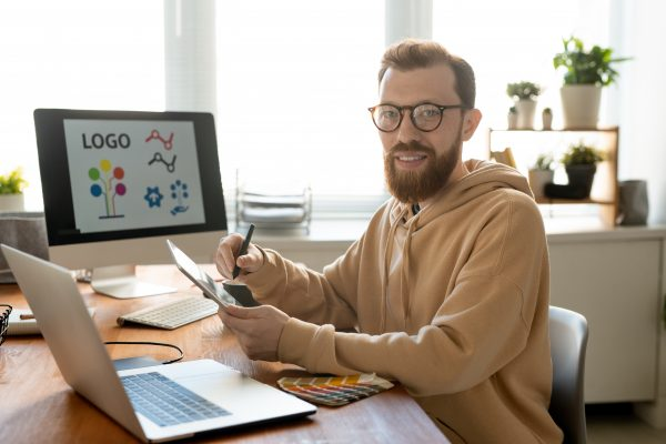 Young cheerful and creative male freelance designer in casualwear and eyeglasses drawing logo in front of laptop and computer monitor